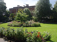 A flower garden and lawn in a park in Exeter